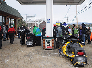 Snowmobilers gas up their sleds
